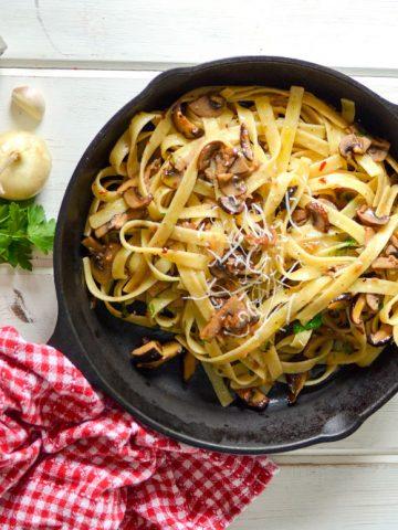 Fettucini with crimini mushrooms in white truffle oil sauce-in the skillet-Parmigiano on the board