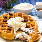 Lemon Blueberry Buttermilk Waffles-one on a plate with fork in and whipped cream