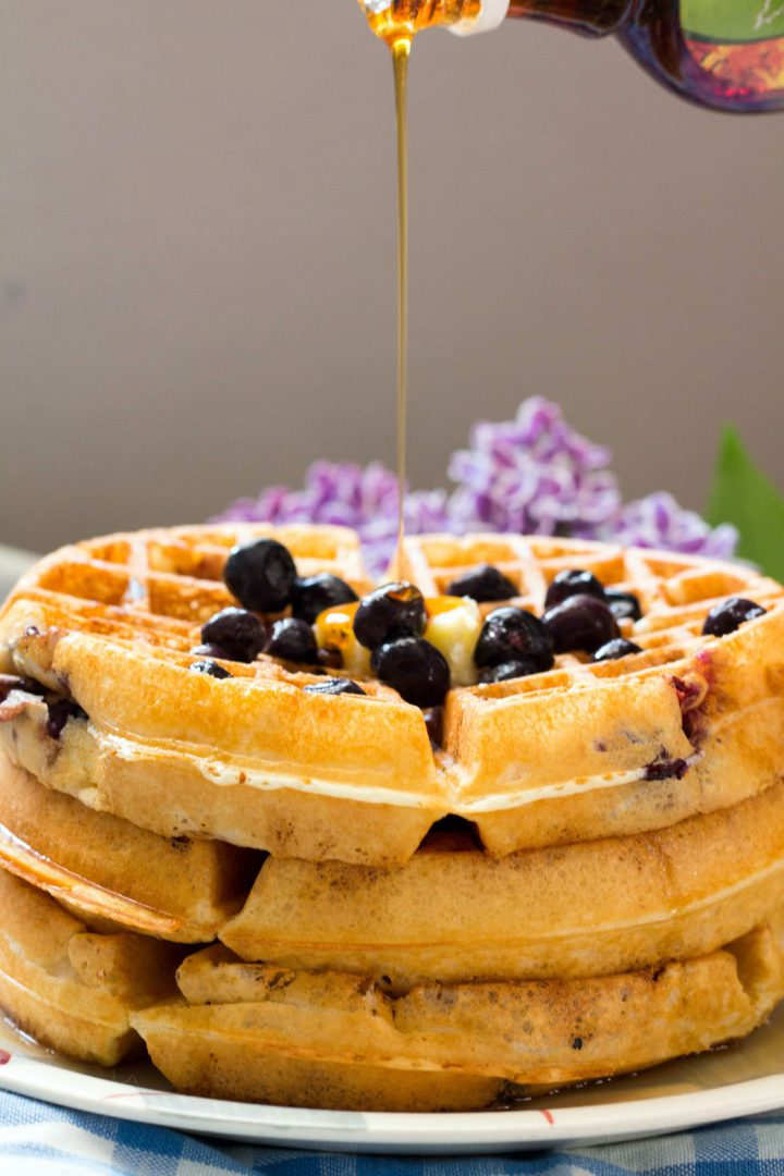Lemon Blueberry Buttermilk Waffles-stack on a plate with blueberries-maple drizzle