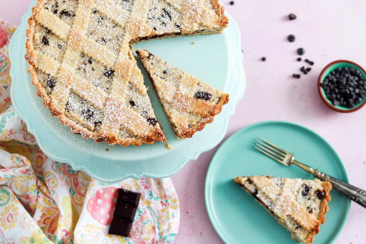 Classic Italian crostata ricotta e cioccolato-feature-slice on a plate-tart on a stand