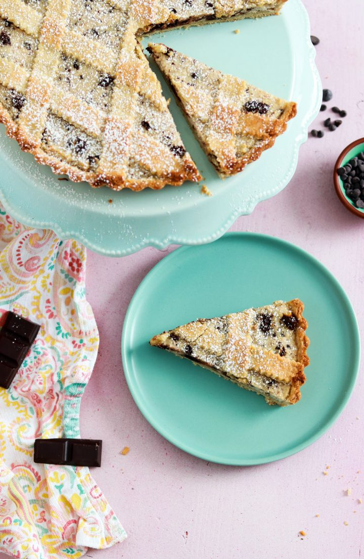 Crostata ricotta e cioccolato-slice on a plate-tart on a stand-view from top