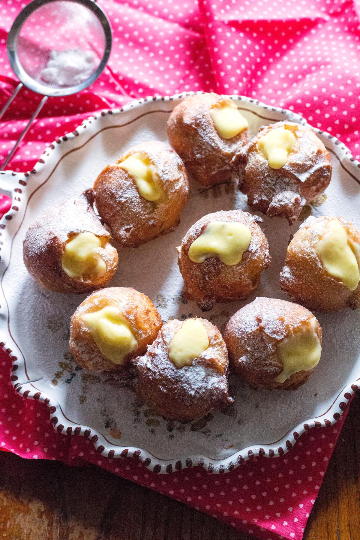 bigne di san giuseppe-puffs on a plate-icing sugar