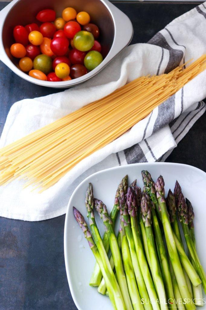 Spaghetti Primavera with Roasted Asparagus and Tomatoes-asparagus, tomatoes and spaghetti on a board