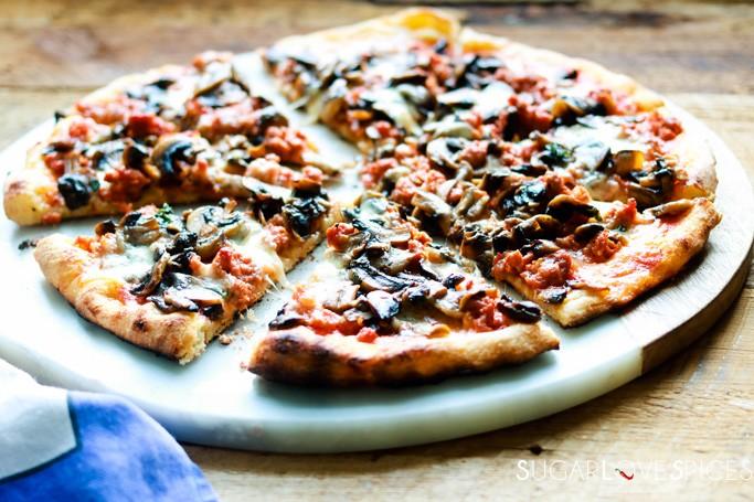 pizza funghi e salsiccia-slices cut on a marble board