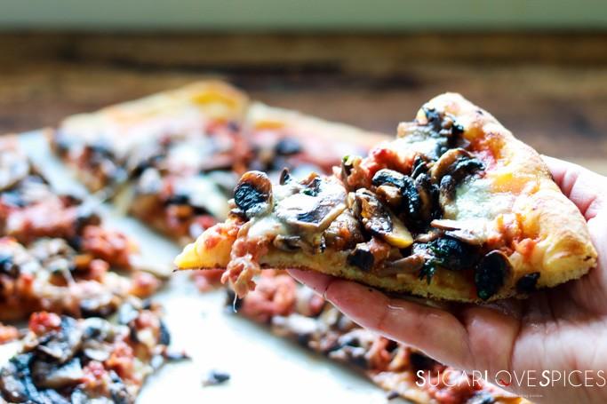 pizza funghi e salsiccia - slice in hand