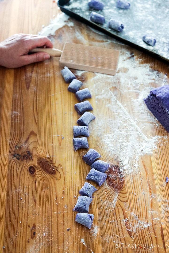 Homemade purple potato gnocchi- cut gnocchi on wood board