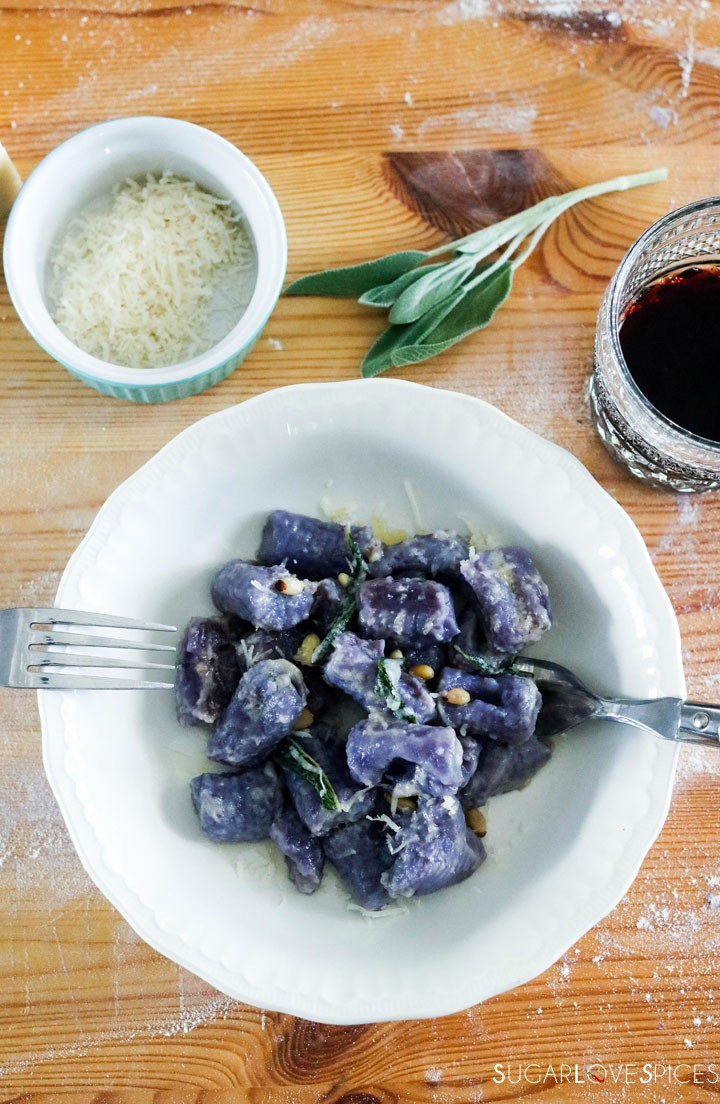 Homemade purple potato gnocchi-plate of cooked gnocchi on board with glass of wine