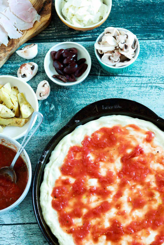 Capricciosa-pizza-adding-tomato-sauce-on-pizza