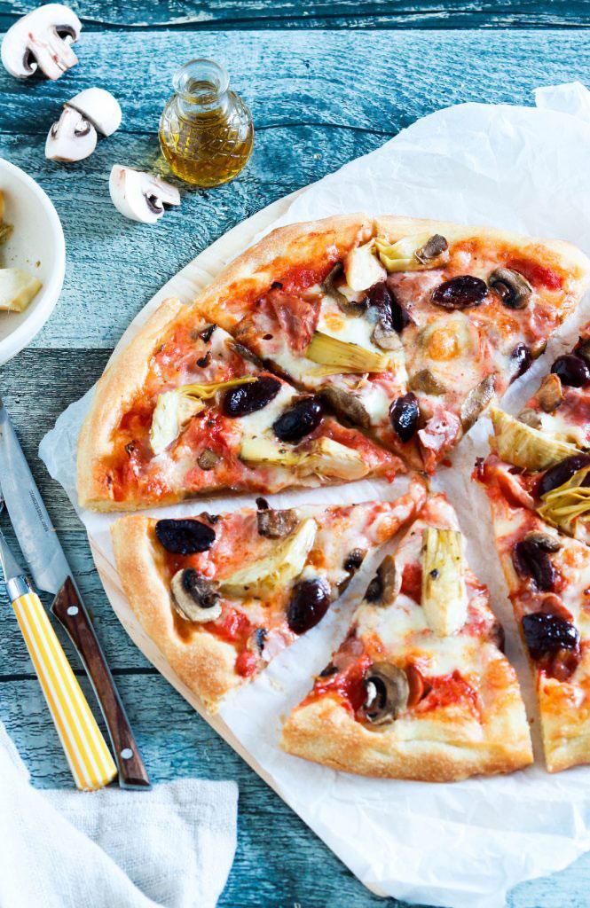 Capricciosa pizza-cut-on parchment paper