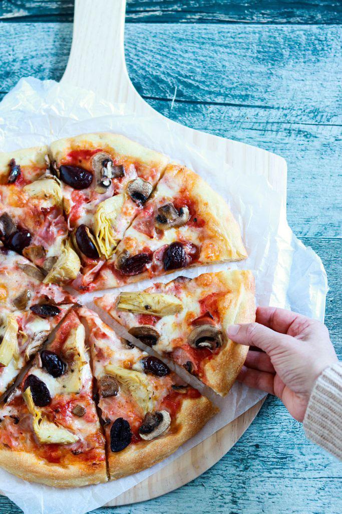 Capricciosa-pizza-hand-on-a-slice