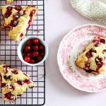 Amazing Cranberry Orange and White Chocolate Scones-feature-one on a plate the rest on a rack