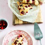 Amazing-Cranberry-Orange-and-White-Chocolate-Scones-one-on-a-plate-the-rest-on-wood-board-top-view