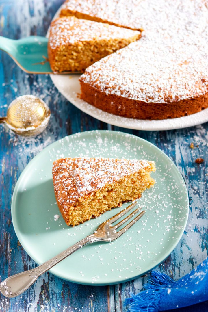 Simple Carrot Almond Cake with Kamut Flour-slice in the plate with fork-cake in background