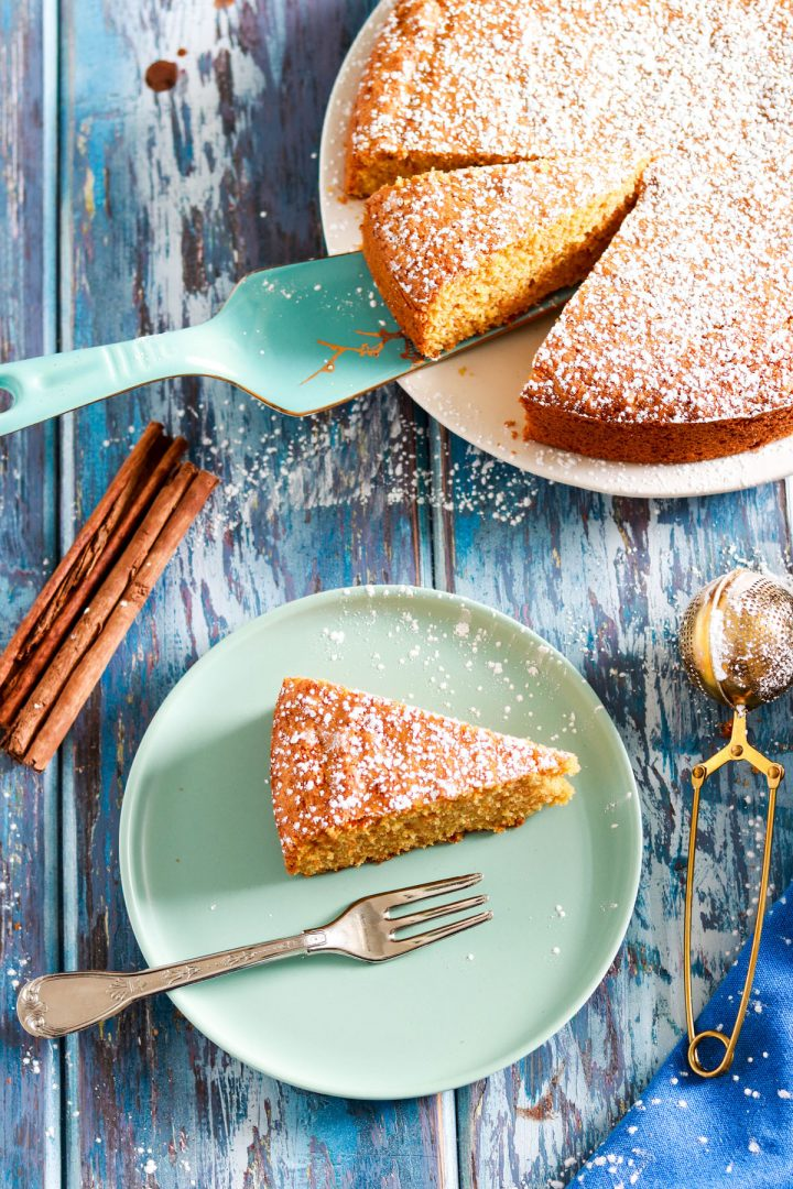 Simple Carrot Almond Cake with Kamut Flour-slice in the plate with fork-cake in background-top view