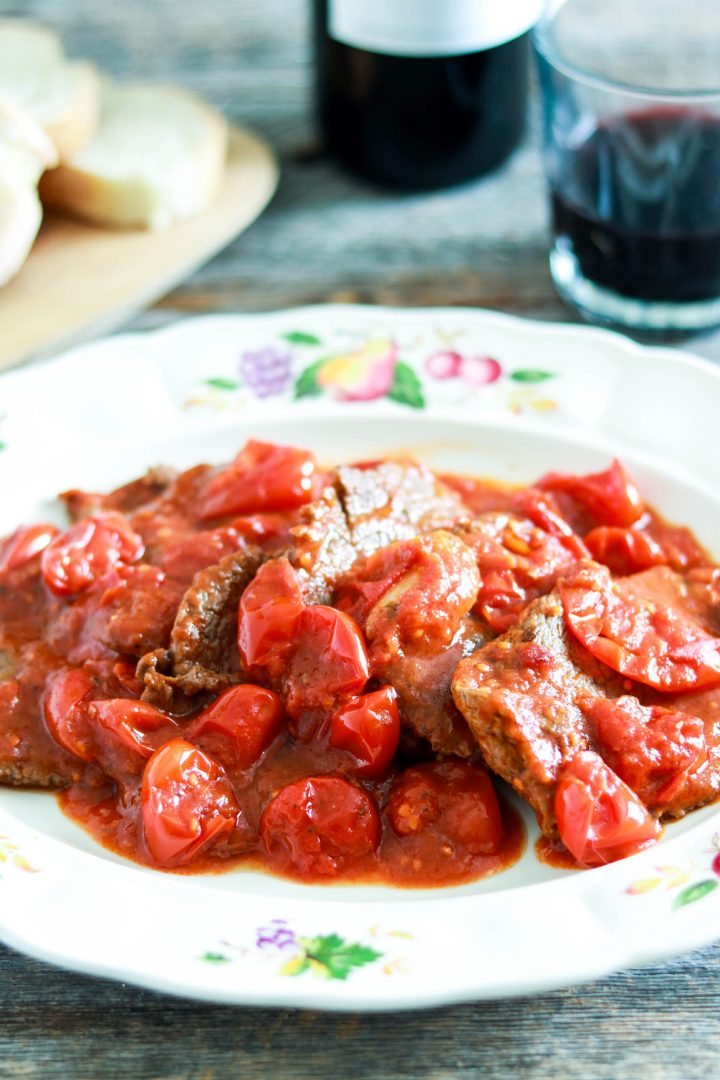 Easy and delicious Mamma's Fettine alla pizzaiola - in the plate-glass of red wine in background