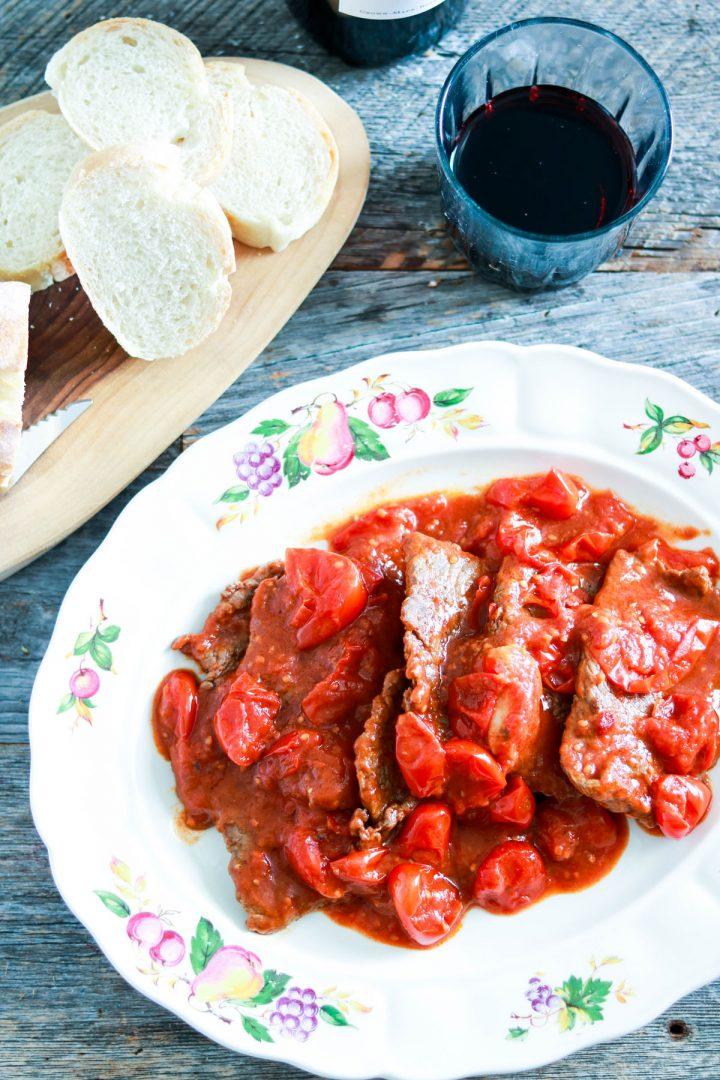 Easy and Delicious Mamma's Fettine alla Pizzaiola - in the plate-top view-wine and bread