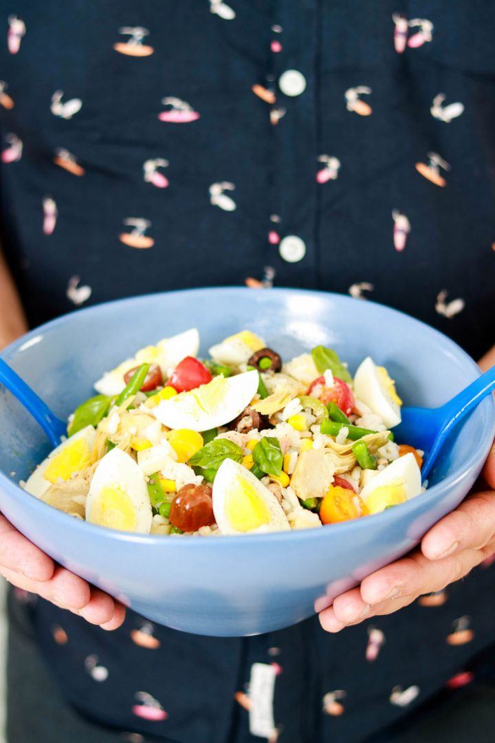 Tasty and Easy Italian Insalata di riso with tuna-hands holding the bowl