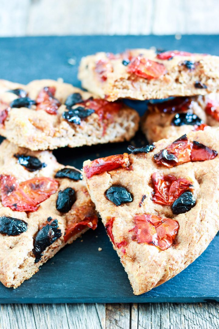 wholemeal spelt focaccia with olives and tomatoes-cut focaccia stacked on a wood board