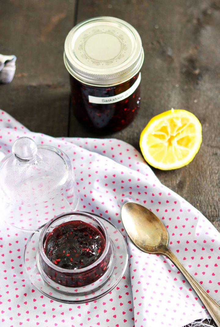 Small batch no-pectin Saskatoon jam-feature-jam in a bowl-jar in background